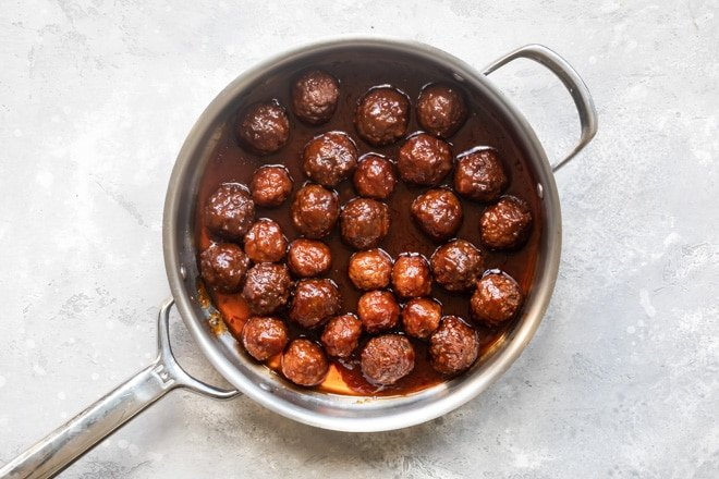 Crockpot meatballs with grape jelly sauce in a silver skillet.
