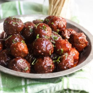 A closeup side shot of crockpot meatballs with grape jelly sauce on a silver place.