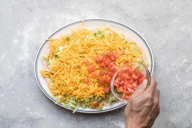 An overhead shot of tomatoes being sprinkled onto easy taco dip on a white platter.