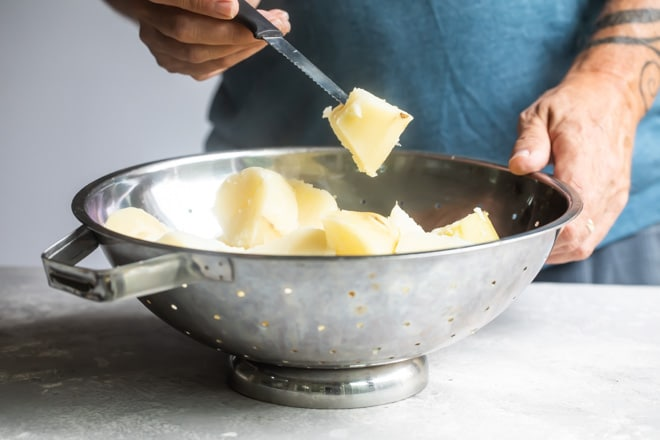 Steamed potatoes in a sliver colander with someone holding a piece of potato on a knife.