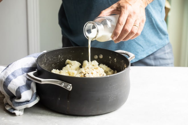 Milk being poured onto mashed potatoes in a black pot.
