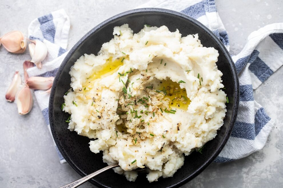 Garlic mashed potatoes in a black bowl with a serving spoon on a blue and white striped towel.