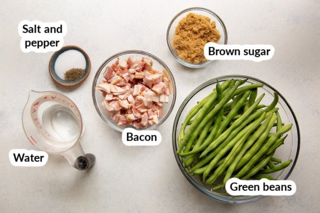 Labeled ingredients for green beans with bacon in various bowls.