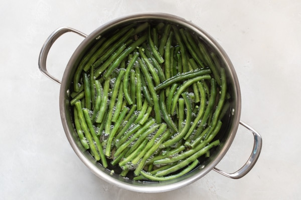 An overhead shot of blanched green beans in a pot.