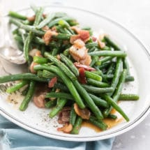A side shot of green beans with bacon on a white platter.