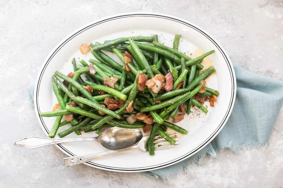 Green beans with bacon on a white platter with a serving spoon and fork.