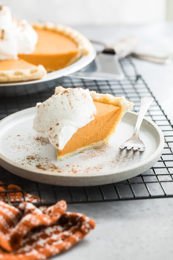 A side shot of make ahead pumpkin pie with whipped cream on a white plate with a silver fork.