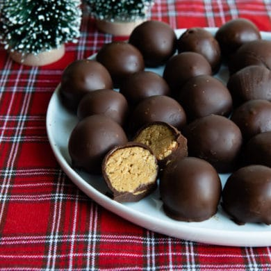No bake peanut butter balls on a white plate.