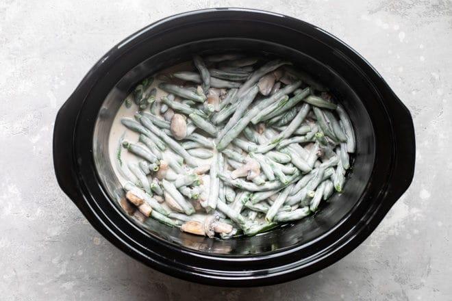 Slow cooker green bean casserole ingredients in a black slow cooker.