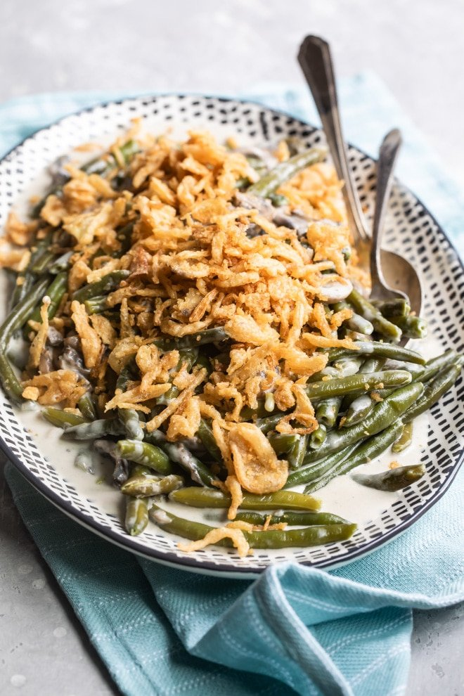 Slow cooker green bean casserole on a black and white serving platter with a serving spoon and fork.