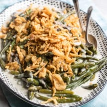 An angled shot of slow cooker green bean casserole on a black and white serving platter with a serving spoon and fork.