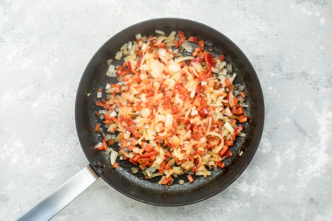 An overhead shot of sweet potato hash ingredients cooking in a black skillet.