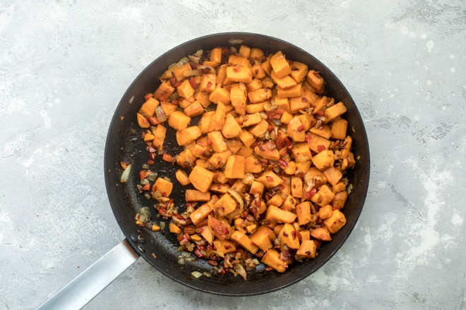 An overhead shot of sweet potato hash cooking in a black skillet.