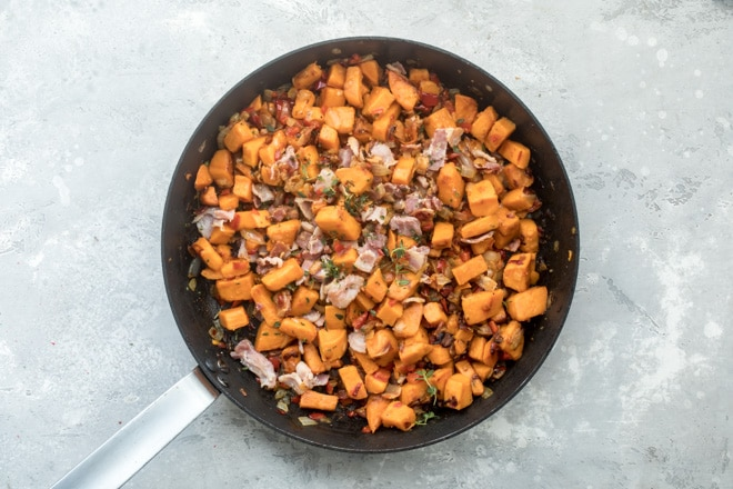 An overhead shot of sweet potato hash in a black skillet.