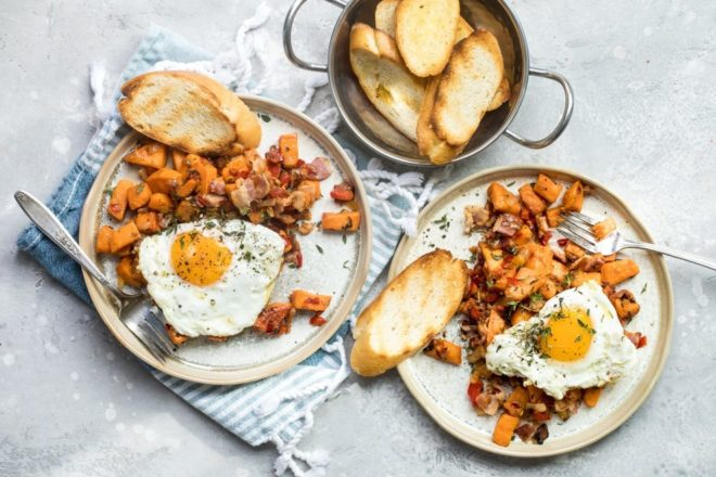 An overhead shot of sweet potato hash on two white plates.