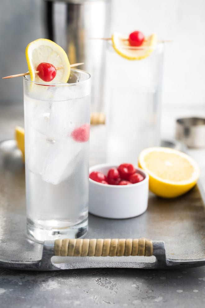 Tom collins in two clear glasses on a silver tray.