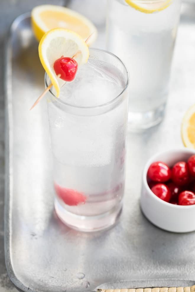 Tom collins in a clear glass with a lemon and cherry.