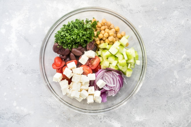 Chickpea salad ingredients in a clear bowl.