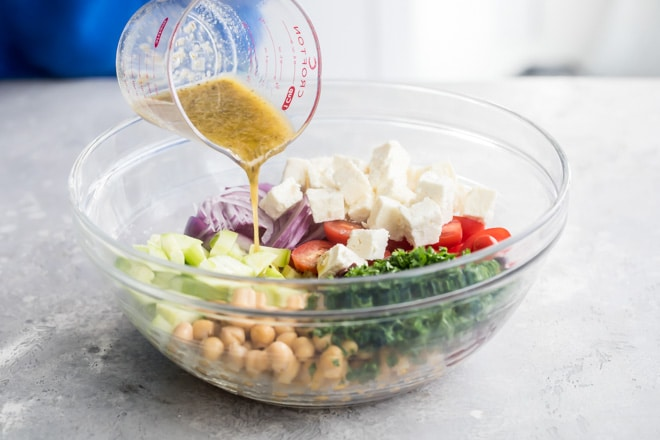 Dressing being poured onto chickpea salad ingredients.