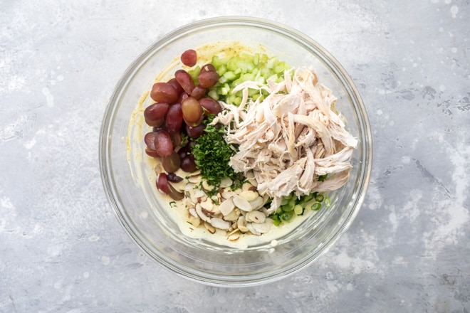 Curried chicken salad ingredients in a clear bowl.