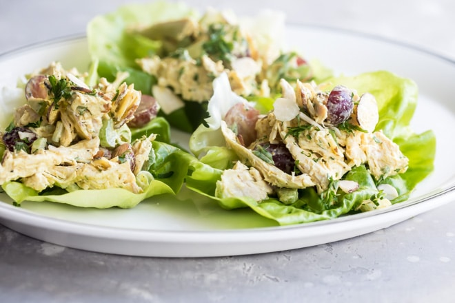 Curried chicken salad on lettuce leaves on a white platter.