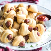 Easy pigs in a blanket on a white plate with a side of ketchup.