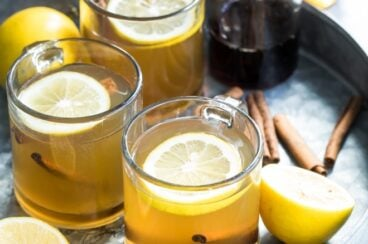 Hot toddies in clear glass mugs on a silver serving tray.