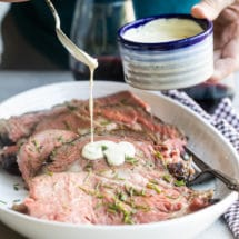 Mustard cream sauce being drizzled onto prime rib slices in a white platter.