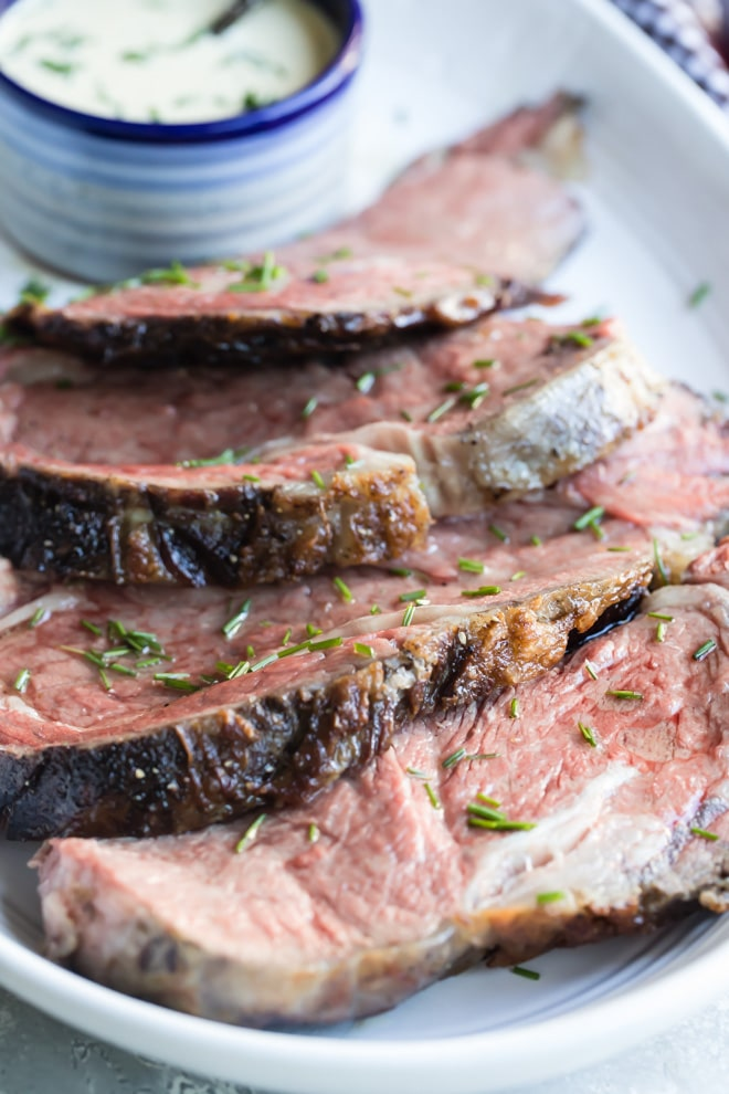 A closeup angled shot of prime rib slices in a white serving bowl.