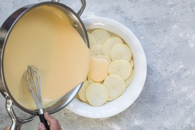 An overhead shot of cheese sauce being poured onto scalloped potatoes in a white serving dish.