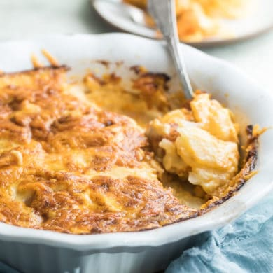 Scalloped potatoes in a white baking dish.