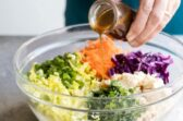 Asian salad dressing being poured into a clear bowl with asian salad ingredients.