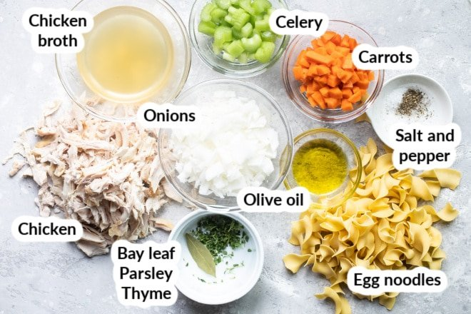 Labeled chicken noodle soup ingredients in bowls.