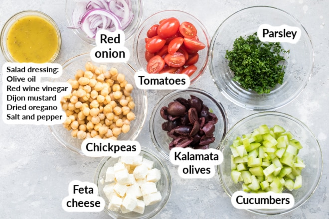 Labeled chickpea salad ingredients in bowls.