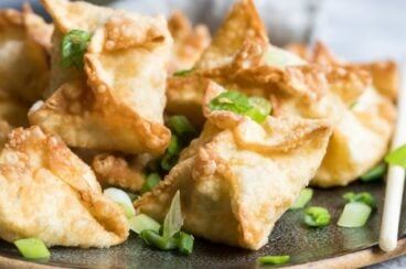 Crab rangoons on a brown platter topped with green onions.