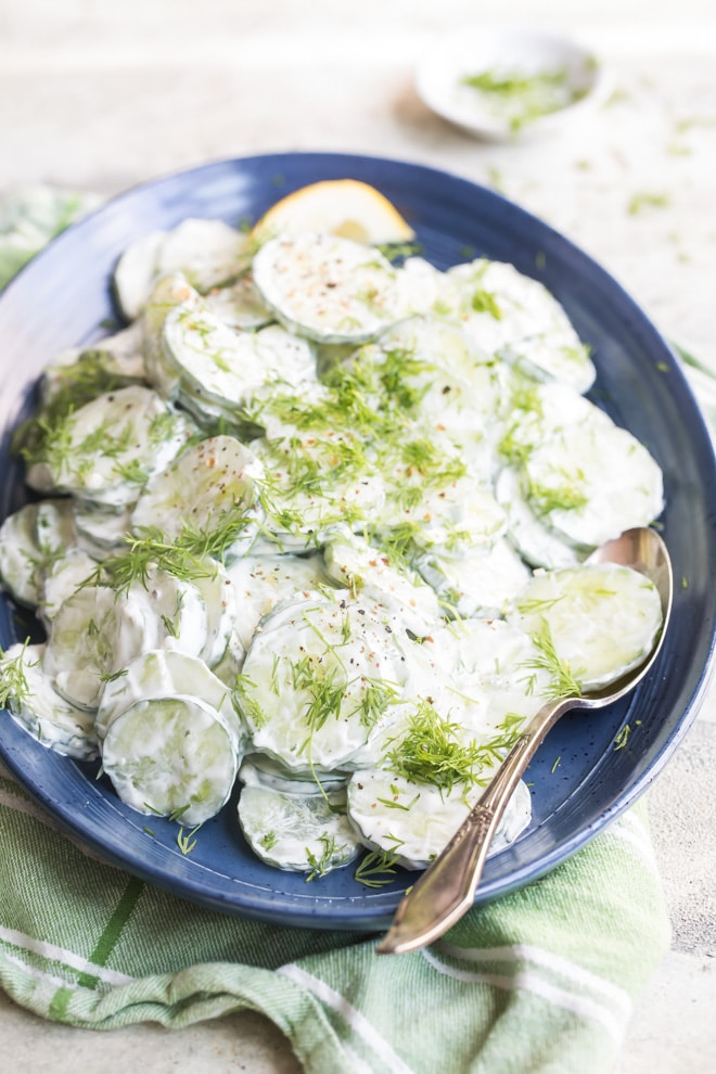 Creamy cucumber salad on a blue plate.