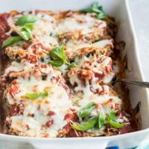 Eggplant parmesan in a white baking dish.