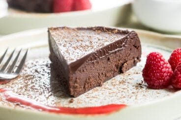 Flourless chocolate cake slice on a white plate.