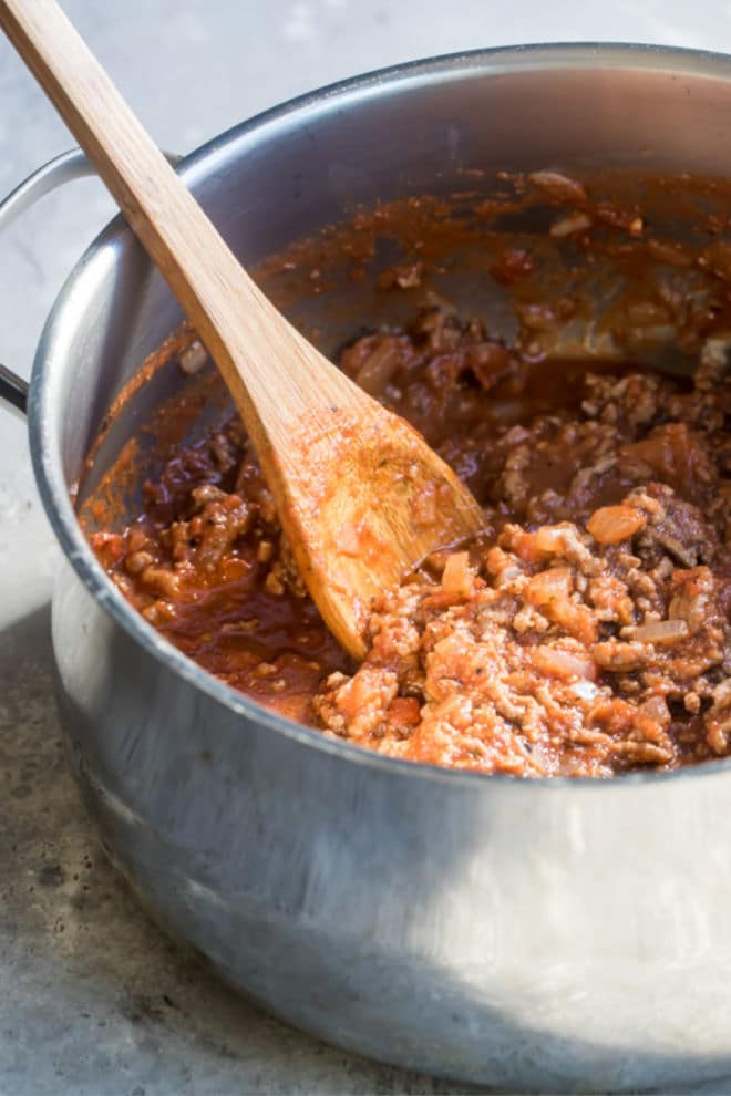 Homemade meat sauce in a silver pot with a wooden spoon.