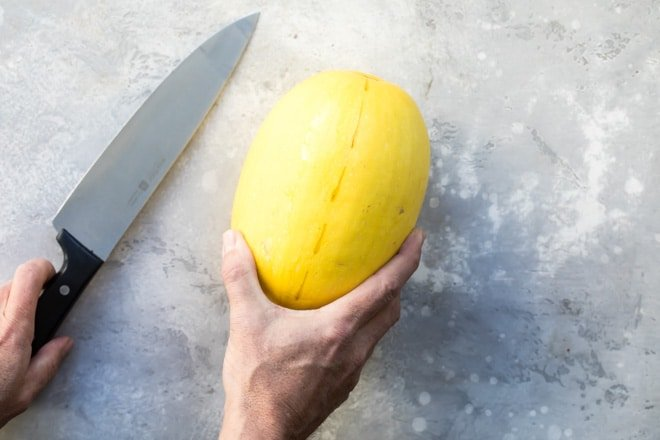 A whole yellow squash and a silver knife.