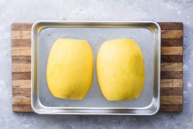 Two halves of a yellow squash on a baking sheet.