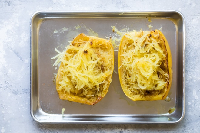 Spaghetti squash on a sliver baking sheet.