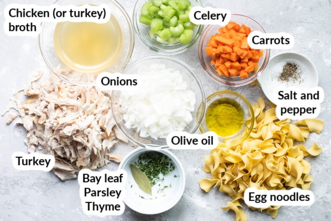 Labeled turkey noodle soup ingredients in bowls.