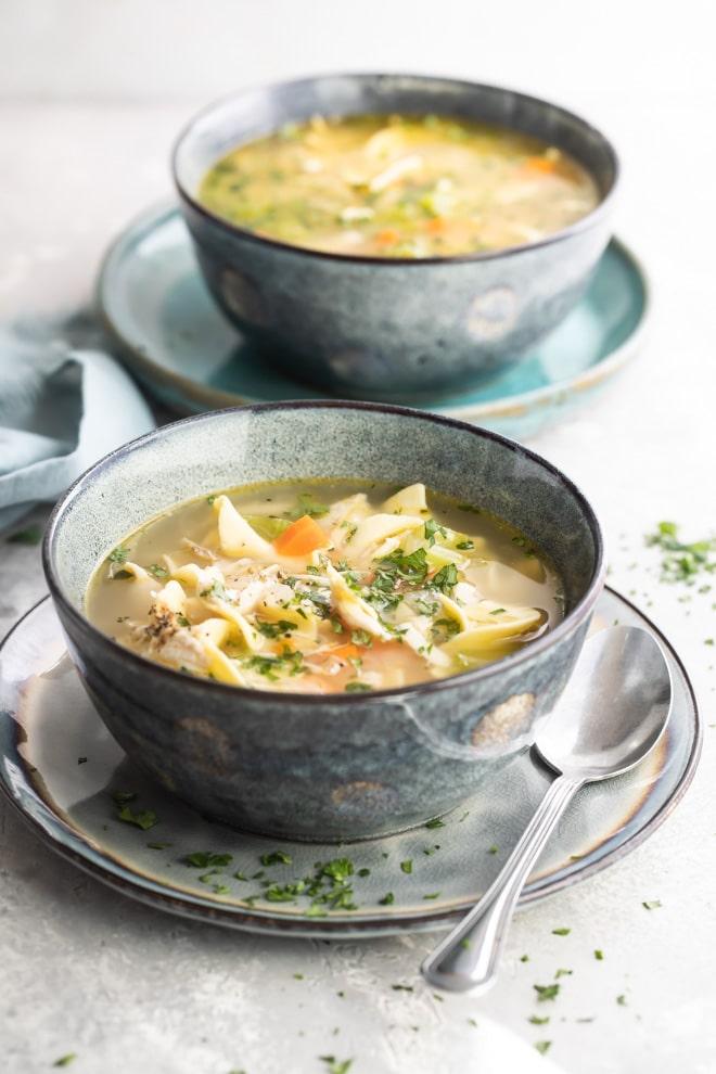 Leftover turkey noodle soup in a blue bowl.