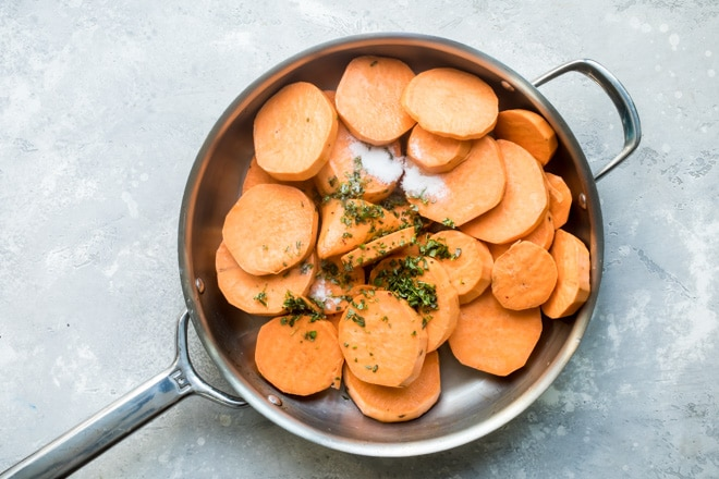 Sliced sweet potatoes and spices in a sliver skillet.