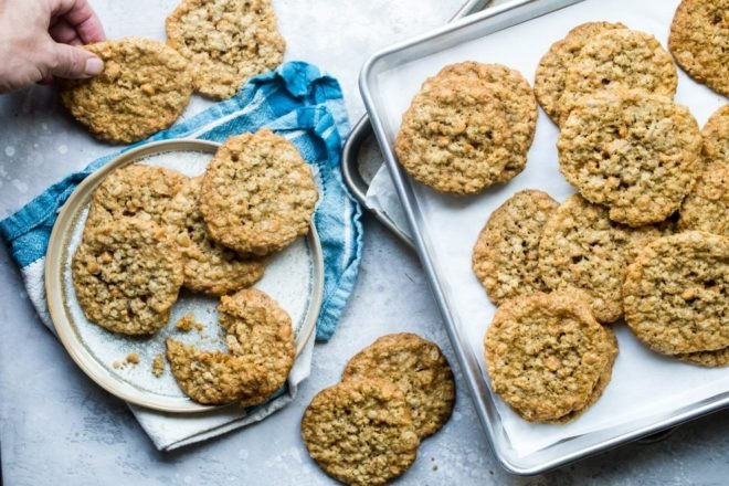 Oatmeal scotchies on a white plate and a silver baking pan.