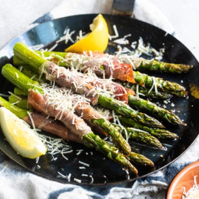 Prosciutto wrapped asparagus on a black plate with shredded Parmesan.