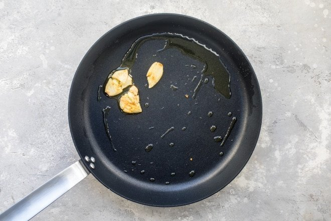 Oil and garlic in a black sauce pan.