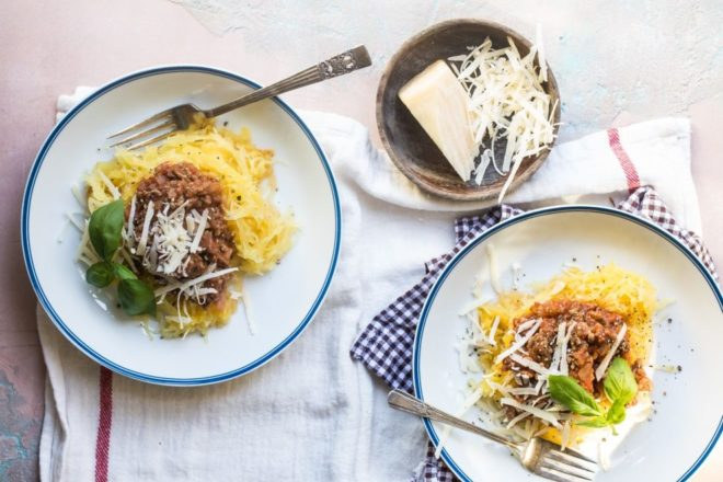 Spaghetti squash with homemade meat sauce on white plates.