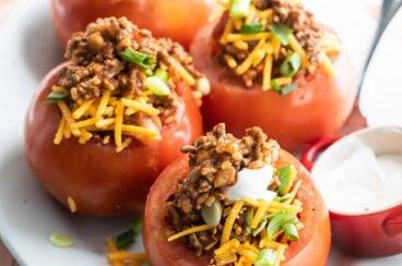 Taco stuffed tomatoes on a white platter.